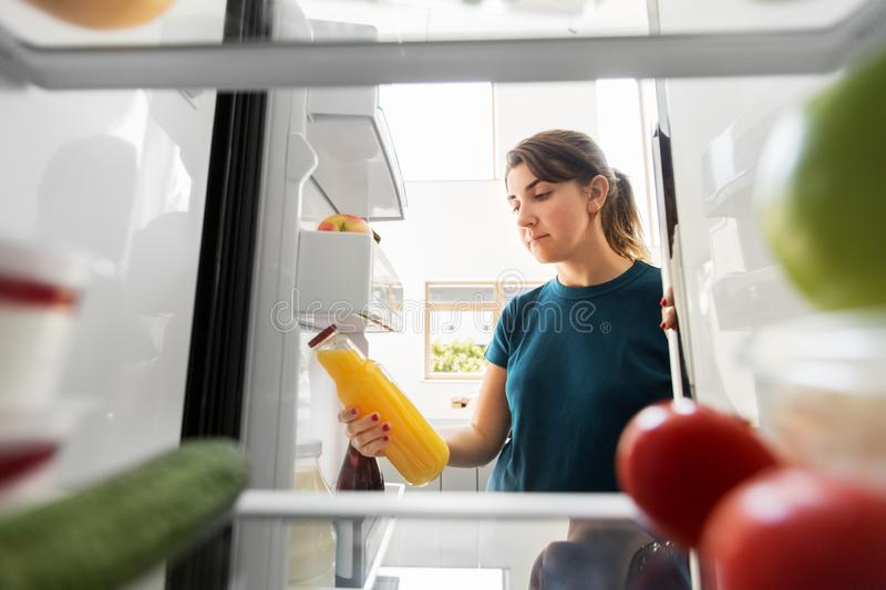 Woman taking bottle of juice from fridge at home stock images