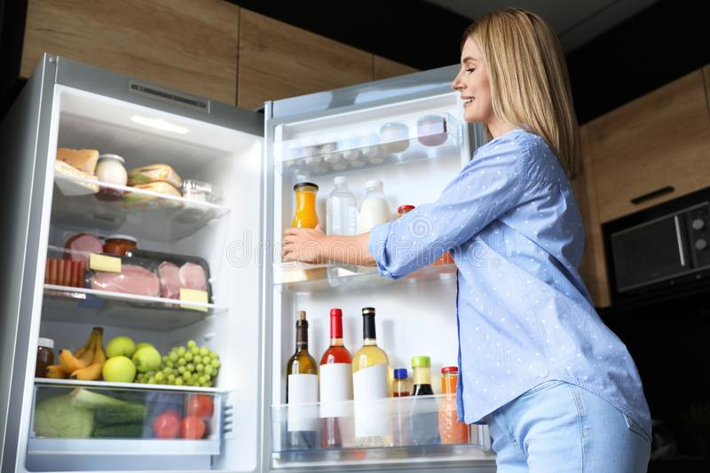 Woman taking bottle with juice out of refrigerator stock photos