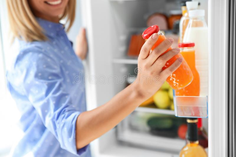 Woman taking bottle with juice out of refrigerator stock photography