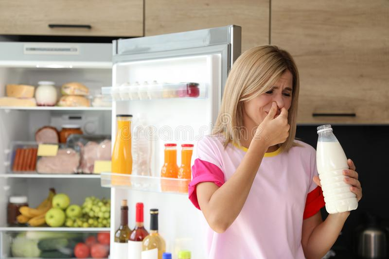 Woman taking bottle with old milk out of refrigerator. In kitchen royalty free stock image