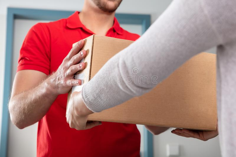 Woman Taking Box From Delivery Man. Close-up Of Woman Taking Cardboard Box From Delivery Man royalty free stock photography