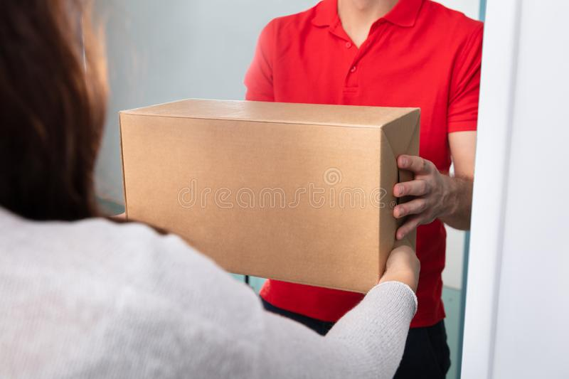 Woman Taking Box From Delivery Man. Close-up Of Woman Taking Cardboard Box From Delivery Man royalty free stock image