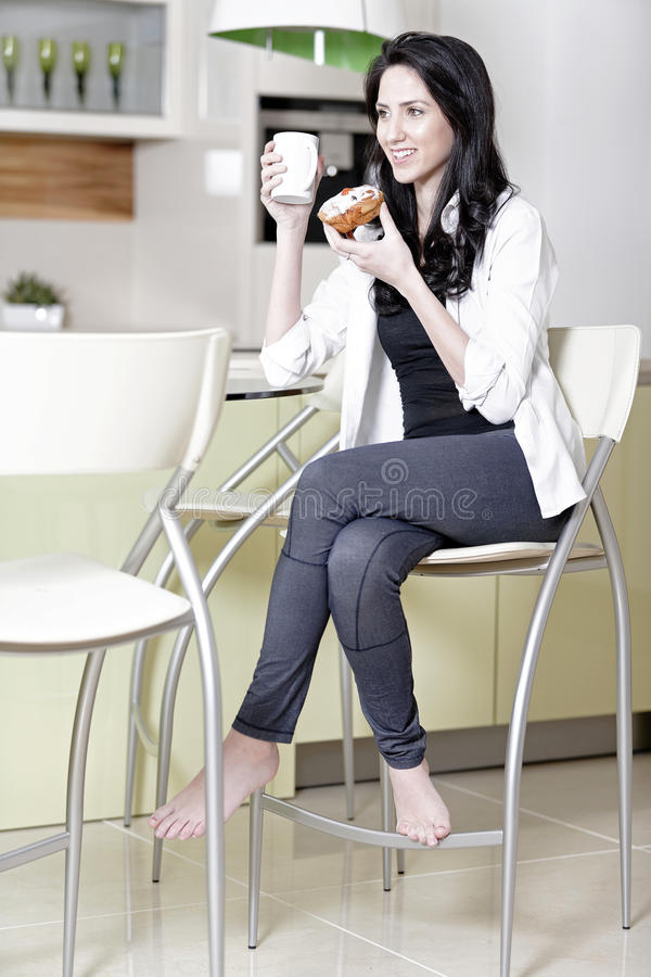 Woman taking a break. Beautiful young woman taking a break in her kitchen with a coffee and cake stock photo