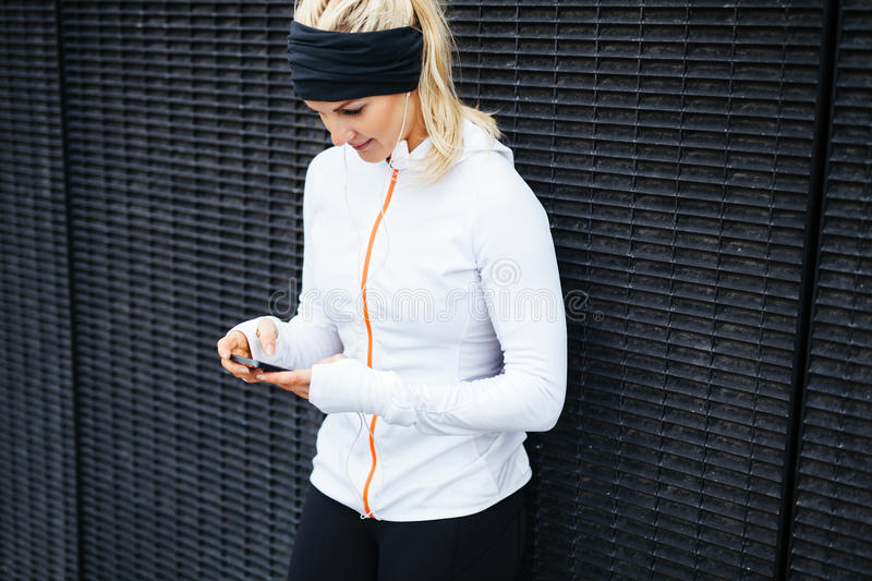 Woman taking a break form workout using mobile phone. Image of young woman taking a break form workout using mobile phone outdoors stock image