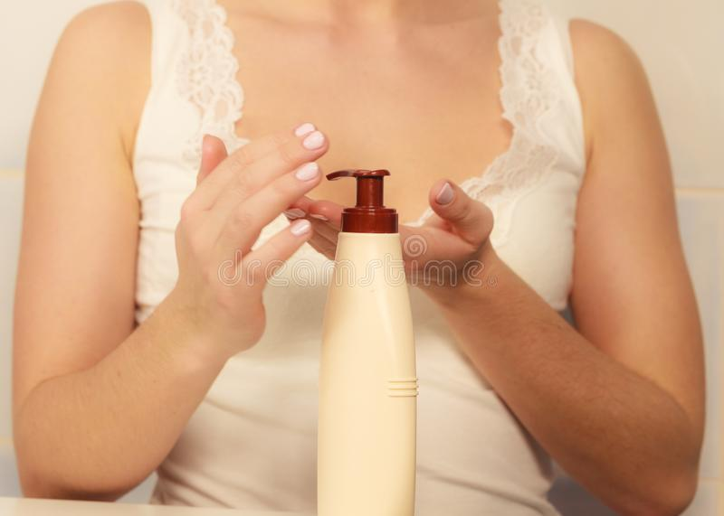 Woman applying moisturizer cream on her body stock photo