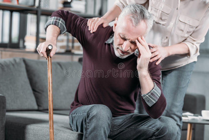 Woman taking care of senior husband with strong headache stock photography