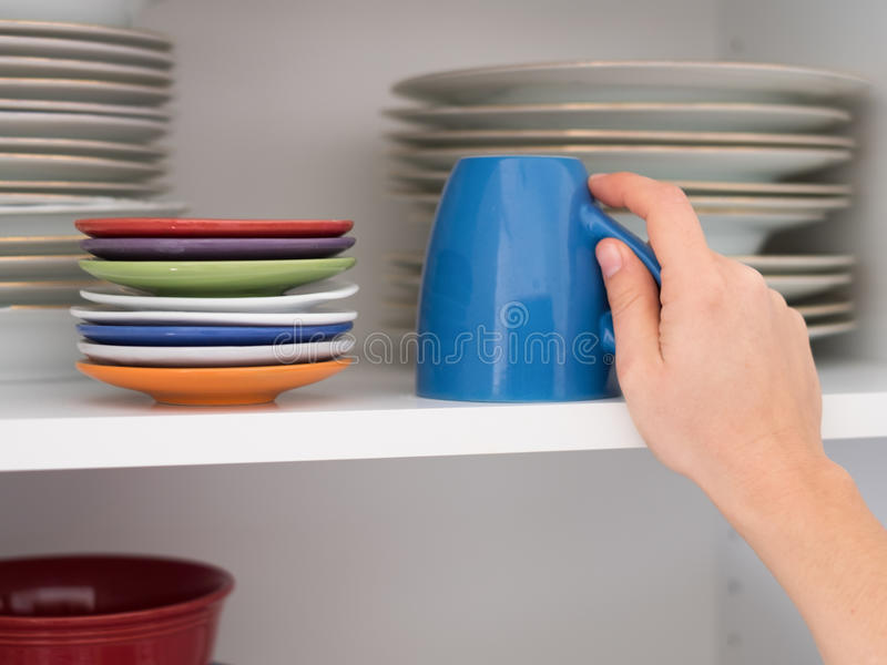 Woman taking a cup from a kitchen cabinet for breakfast. Woman taking a cup from a kitchen cabinet f stock image