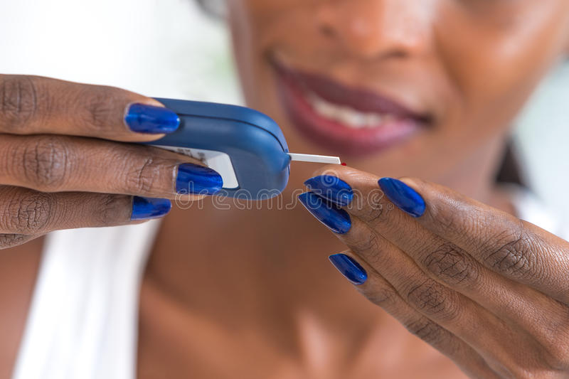 Woman taking diabetes test with glucometer stock photography