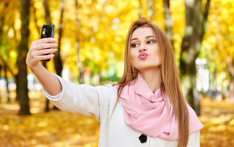 Woman taking duckface selfie in autumn city park. Woman taking duckface selfie portrait in autumn city park royalty free stock photos