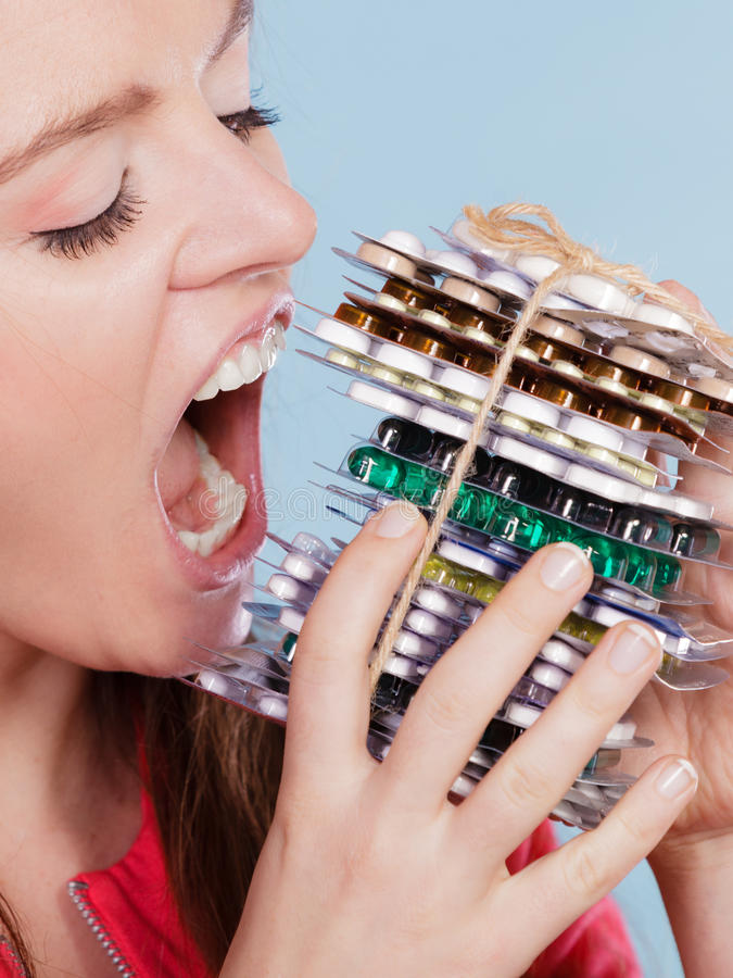 Woman taking eating pills tablets. Drug addict. Woman taking pills. Girl female eating stack of tablets. Drug addict and health care concept. Overdose stock photography