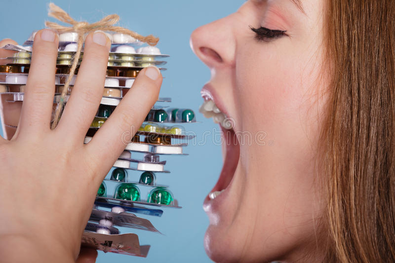 Woman taking eating pills tablets. Drug addict. royalty free stock images