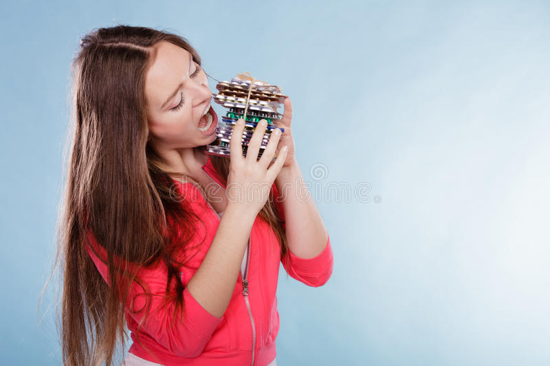 Woman taking eating pills tablets. Drug addict. Woman taking pills. Girl female eating stack of tablets. Drug addict and health care concept. Overdose royalty free stock images