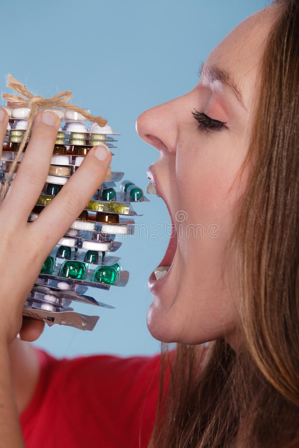Woman taking eating pills tablets. Drug addict. Woman taking pills. Girl female eating stack of tablets. Drug addict and health care concept. Overdose royalty free stock photo