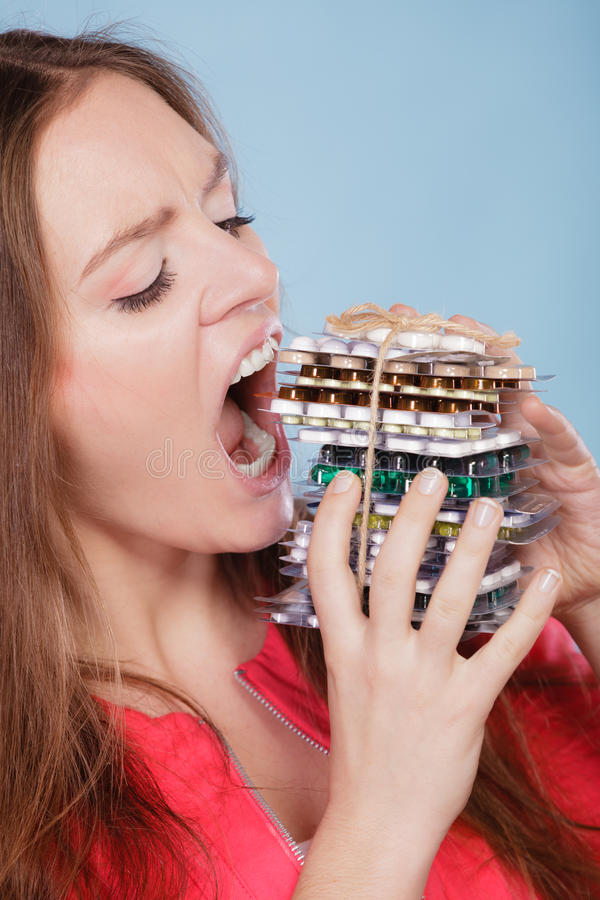 Woman taking eating pills tablets. Drug addict. Woman taking pills. Girl female eating stack of tablets. Drug addict and health care concept. Overdose stock photo