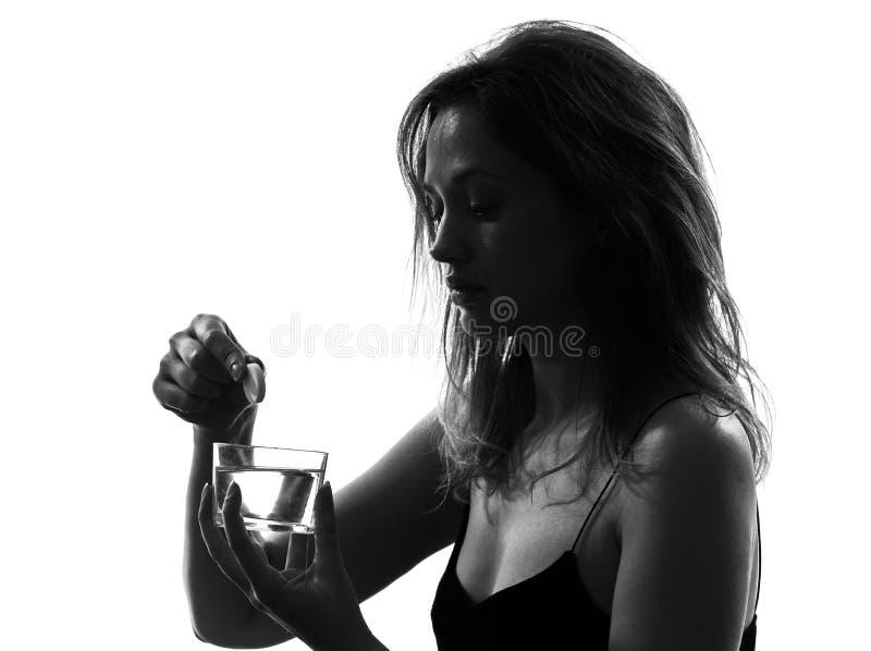 Woman taking effervescent medicine portrait silhouette. One woman taking effervescent medicine portrait silhouette studio on white background royalty free stock image