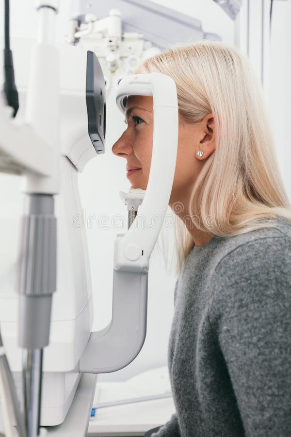 Woman taking eyesight test at optician`s office. royalty free stock images