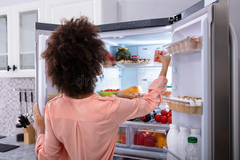 Woman Taking Food From Refrigerator. Rear View Of A Young Woman Taking Food To Eat From Refrigerator stock photos