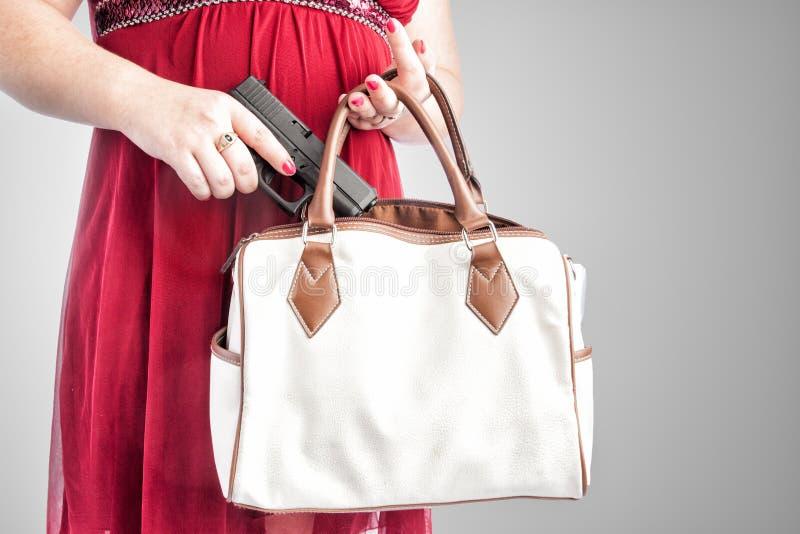Woman taking gun from purse stock photo