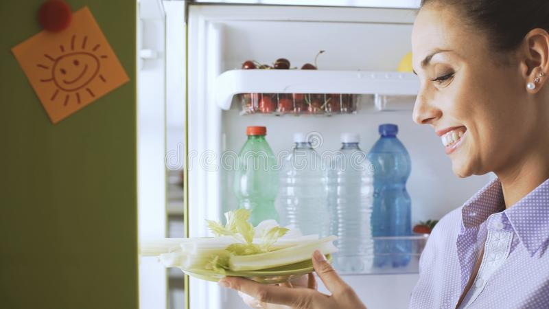 Woman taking healthy vegetables from the fridge. Young woman taking fresh healthy vegetables from the fridge and preparing lunch, diet and lifestyle concept stock image