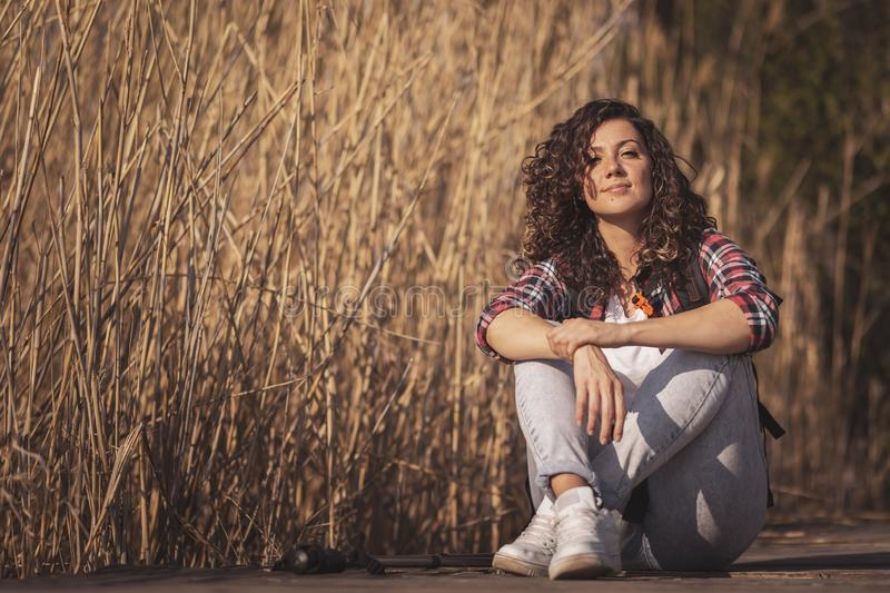 Woman taking a hiking break. Woman sitting on the wooden lake docks, taking a break from hiking in nature, relaxing and enjoying a sunny autumn day royalty free stock photography
