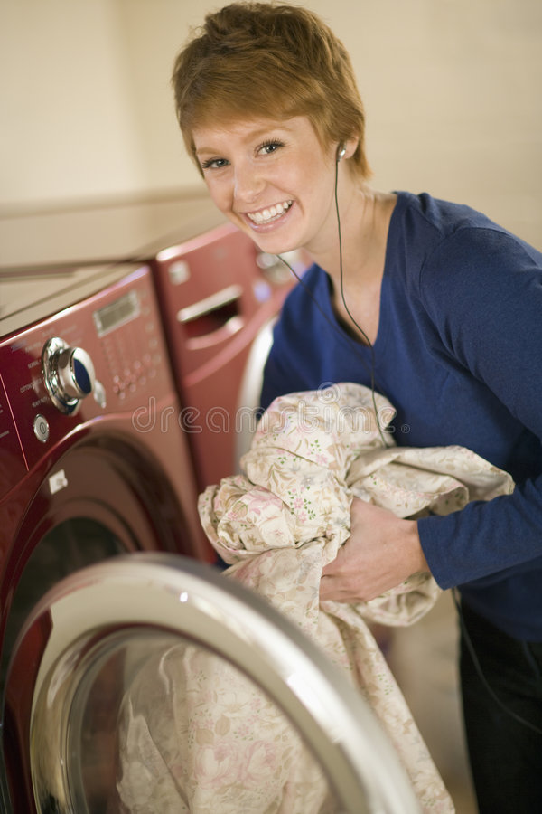 Woman taking laundry out of dryer. Smiling woman with earphones taking laundry out of dryer royalty free stock photos