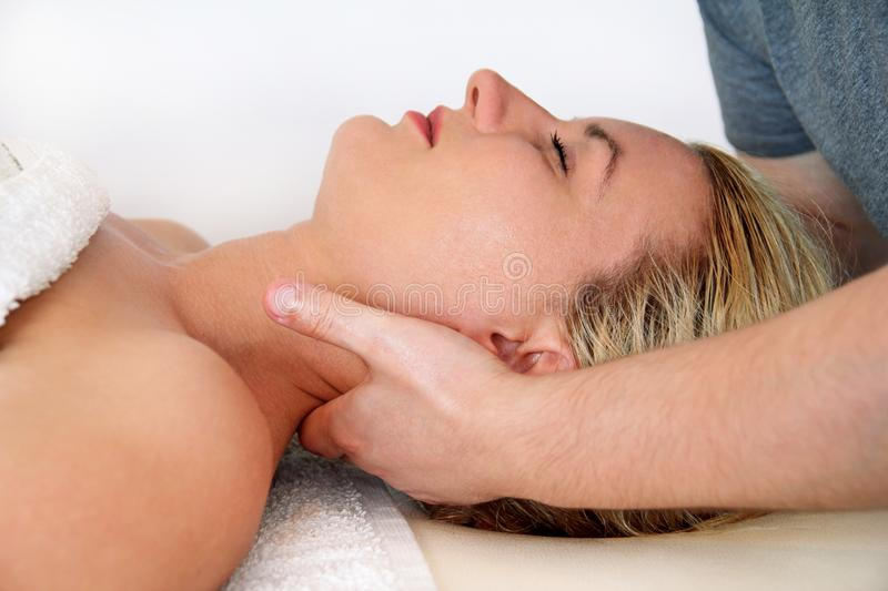 Woman taking a massage neck muscles at massage table. Beautiful women during and enjoying, receiving a wellness neck massage in spa center, she is very relaxed royalty free stock photo