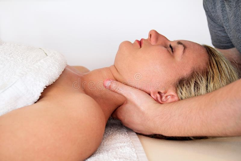 Woman taking a massage neck muscles at massage table. Massage relax studio. Woman taking a massage neck muscles at massage table. Body care. Spa body massage stock image