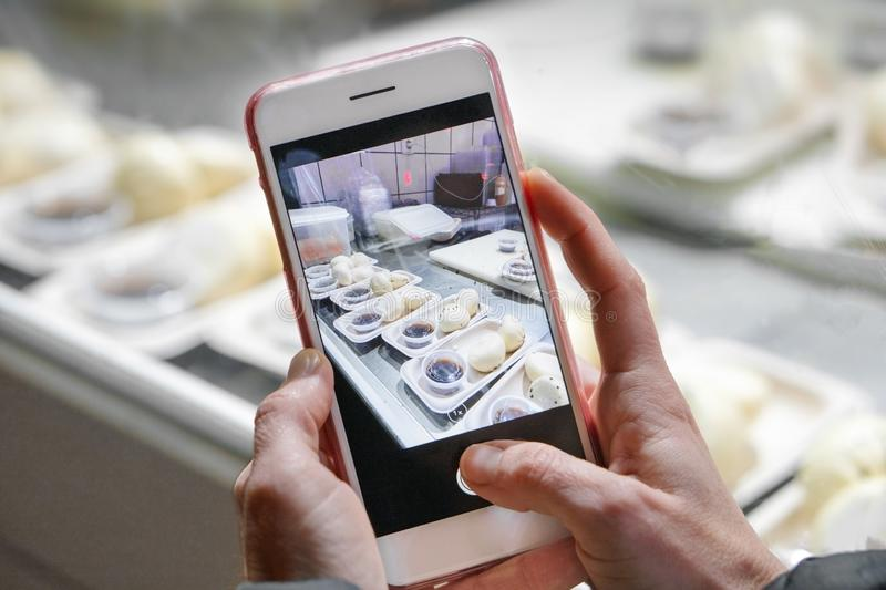 Woman is taking mobile photo of asian food preparation at a restaurant showcase. Woman is taking mobile photo of asian food preparation at a restaurant showcase stock photo