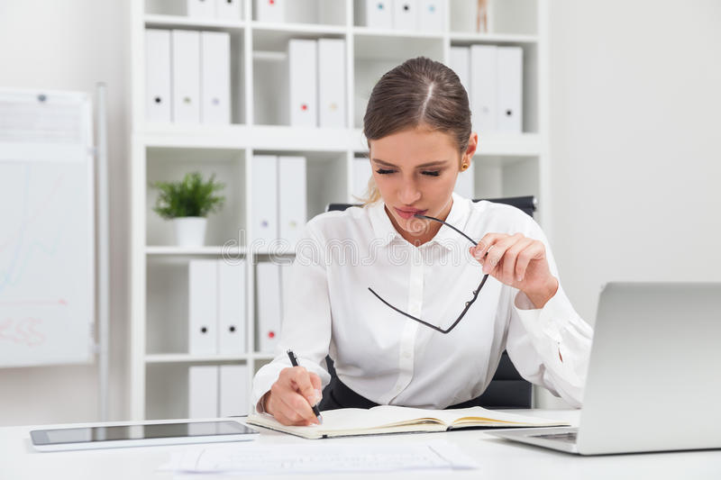 Woman taking notes. Business lady taking notes and thinking sitting at her workplace in company office. Concept of busy day at work stock photography
