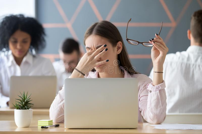 Woman taking off glasses tired of work, eyes fatigue concept stock photos