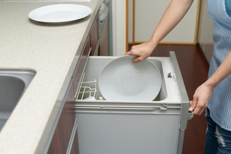 Woman taking out dishware of the dishwasher stock photo