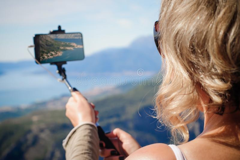 Woman taking panoramic picture of mountain landscape. Selfie photo stick royalty free stock photo