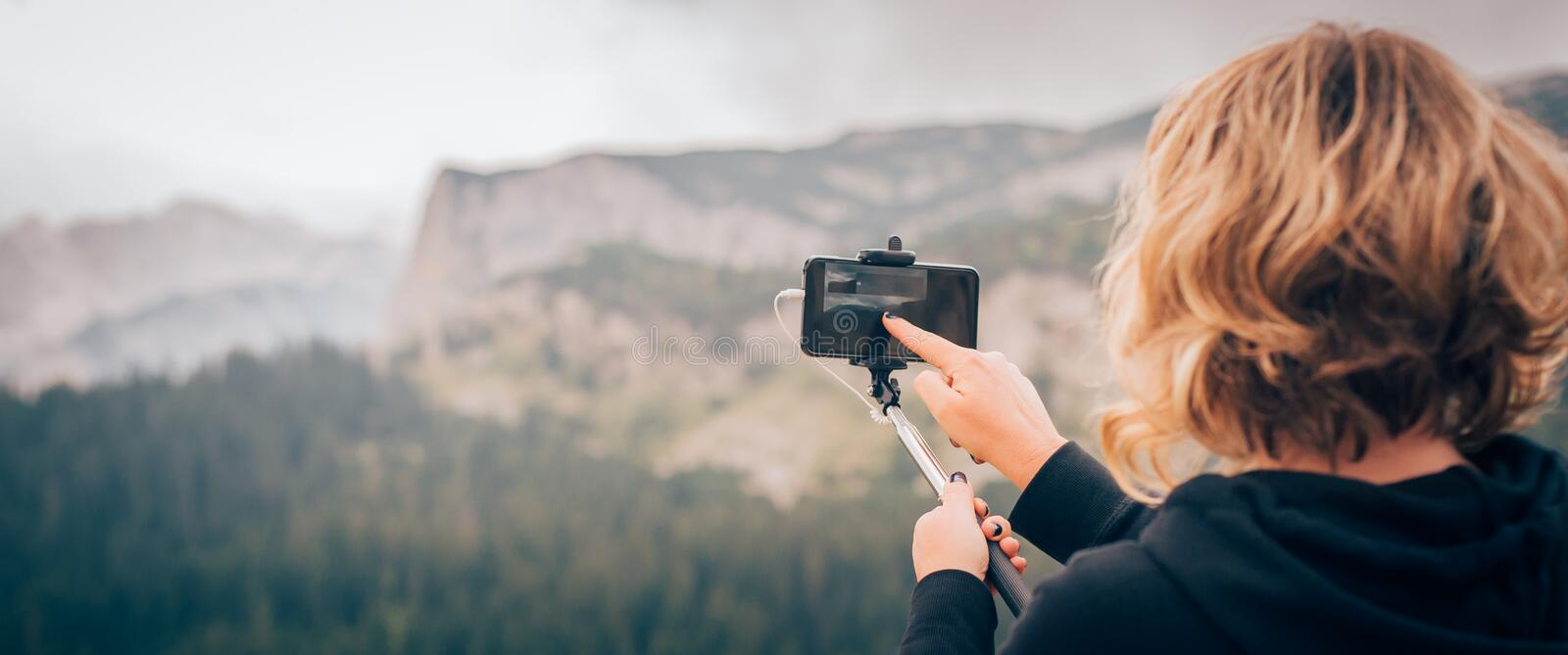 Woman taking panoramic picture of mountain landscape. Selfie photo stick stock image