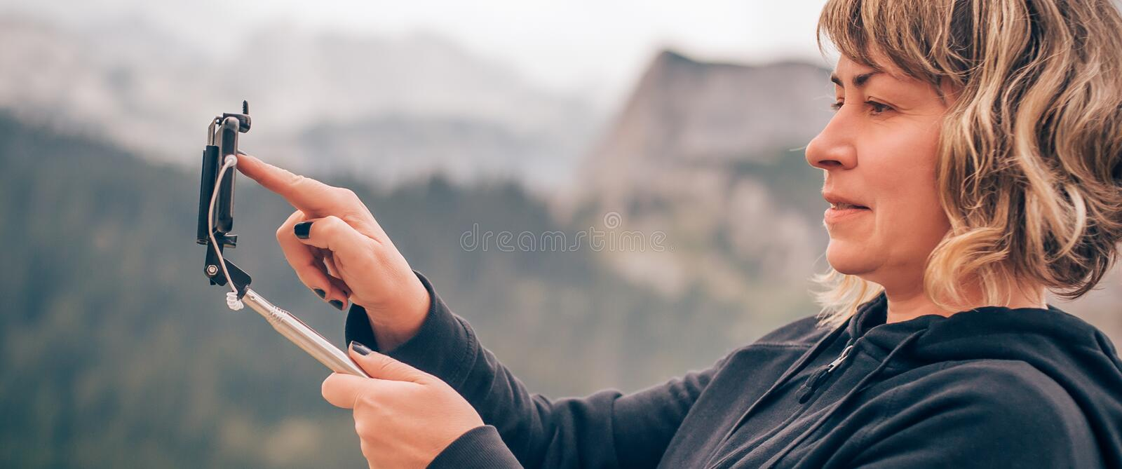 Woman taking panoramic picture of mountain landscape. Selfie photo stick stock photo