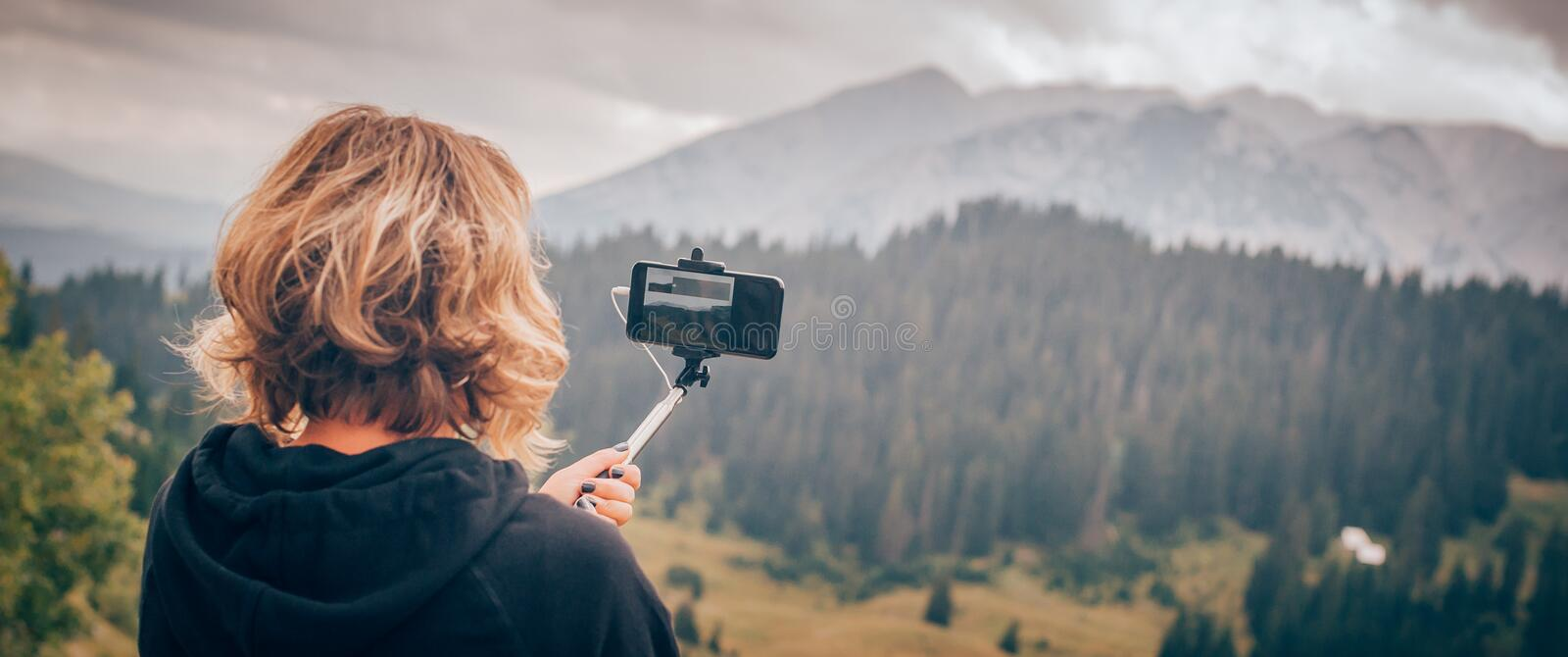 Woman taking panoramic picture of mountain landscape. Selfie photo stick royalty free stock photos