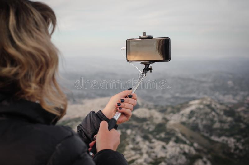 Woman taking panoramic picture of mountain landscape. Selfie photo stick stock images
