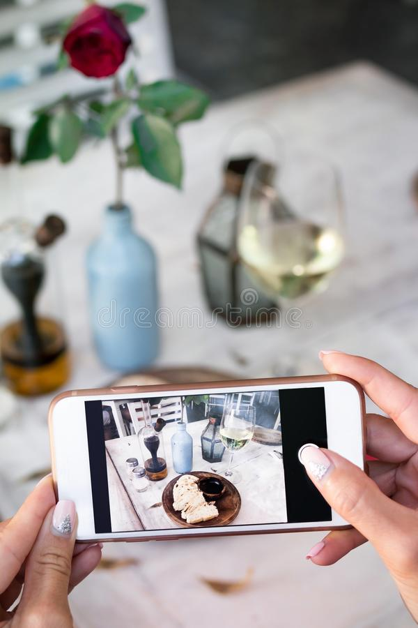 Woman taking photo of bread and wine on her smartphone in restaurant. Bali stock image