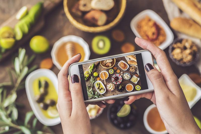 Woman taking a photo of breakfast table royalty free stock photos