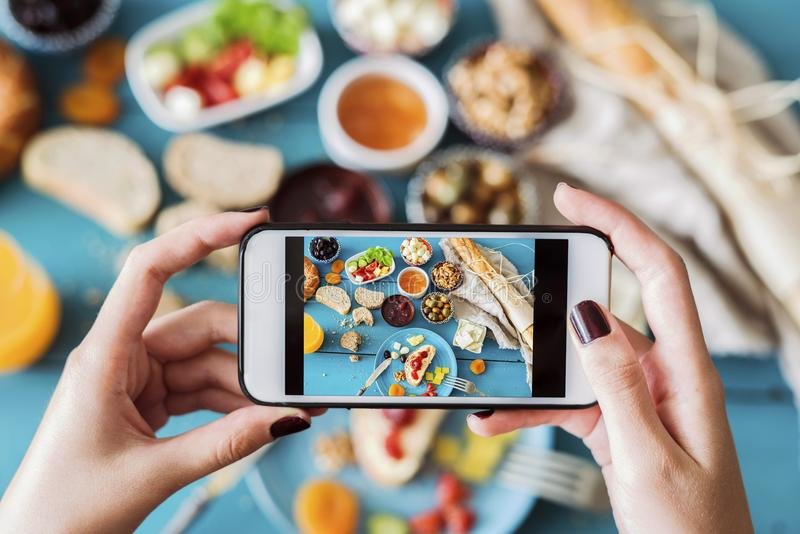 Woman taking a photo of breakfast table stock images