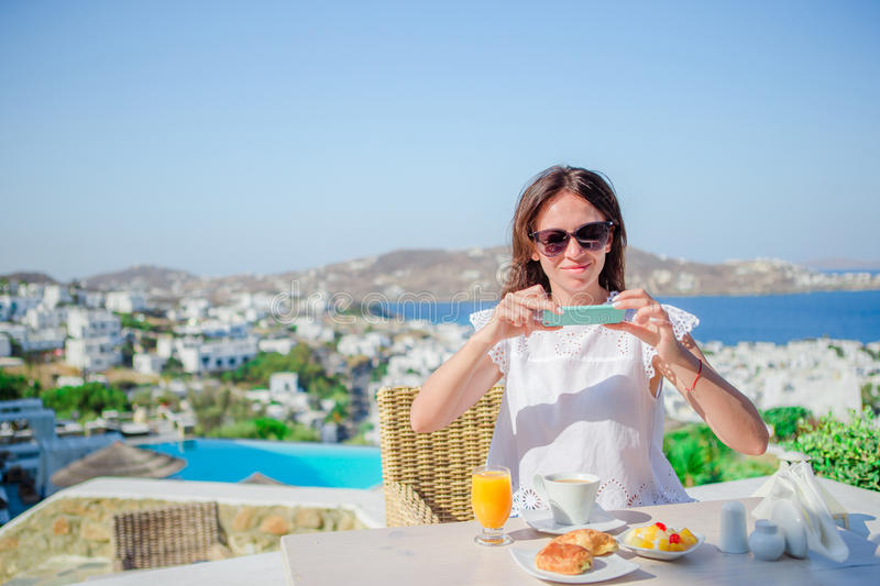 Woman taking photo of breakfast using her phone with amazing view of Mykonos. Girl taking pictures of food on luxury. Woman having breakfast at outdoor cafe with royalty free stock images