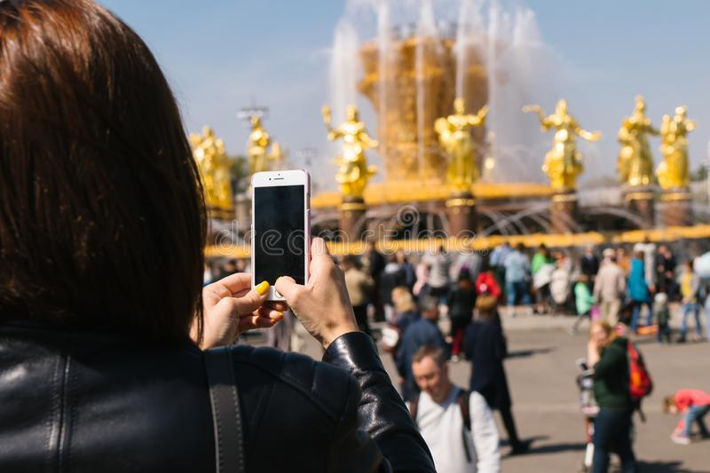 Woman taking photo of Fountain of friendship of nations in VDNH, Russia, Moscow. royalty free stock images