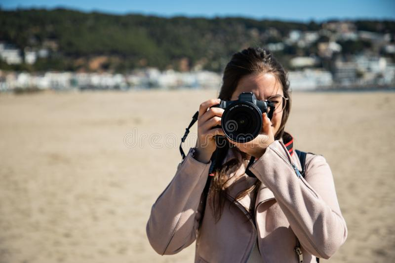 Woman taking photo front view with DSLR camera stock photos