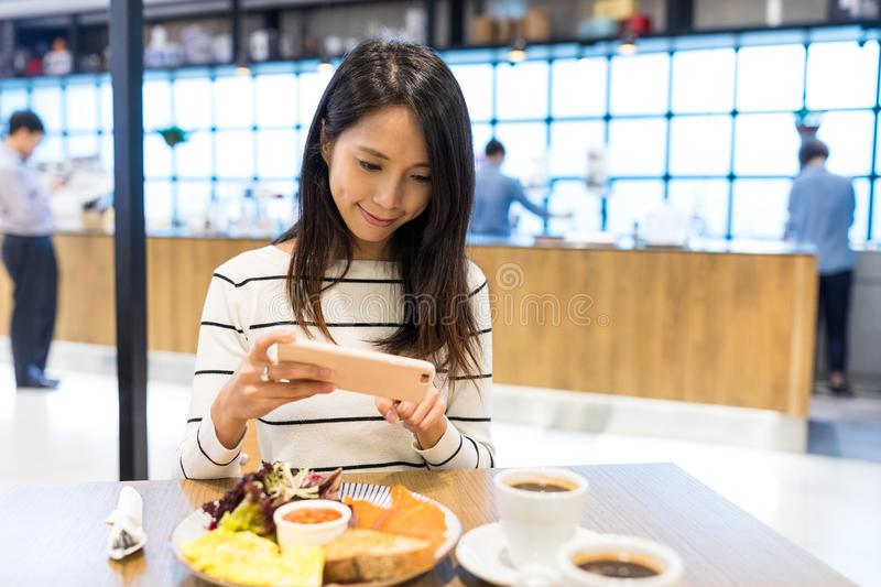 Woman taking photo on her dish in restaurant royalty free stock photography