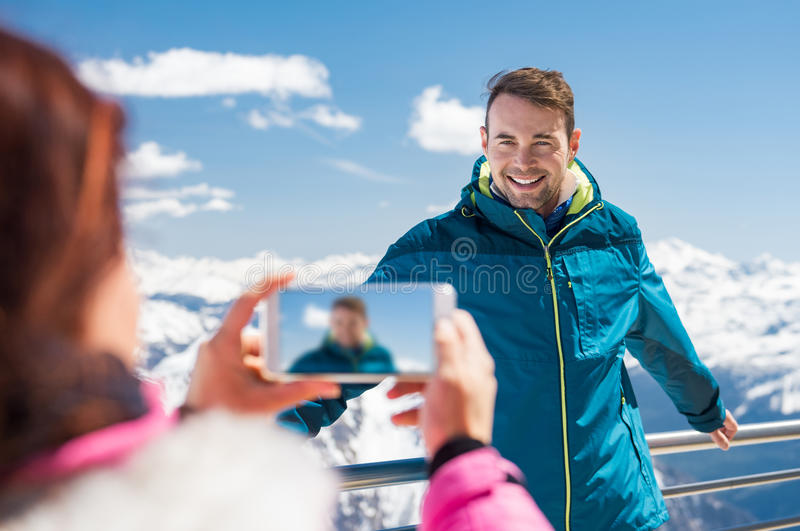 Woman taking a photo of her man royalty free stock photo