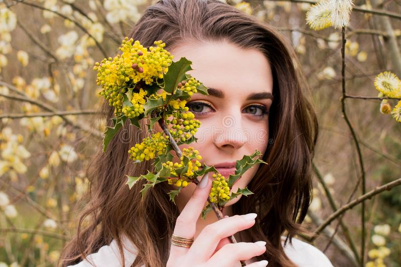 Woman Taking Photo With Holding Yellow Flower Buds at Daytime royalty free stock images