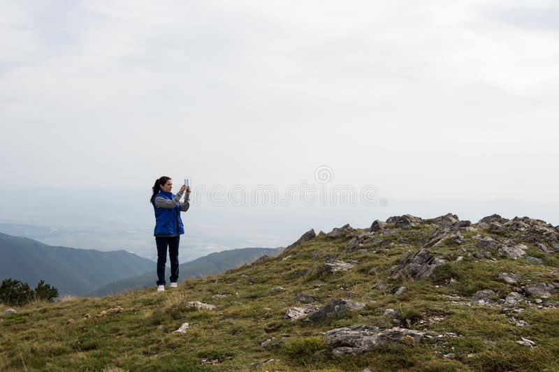 Woman taking photo with mobile cell phone stock images
