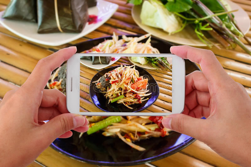 Woman taking a photo of papaya salad with smartphone stock photo
