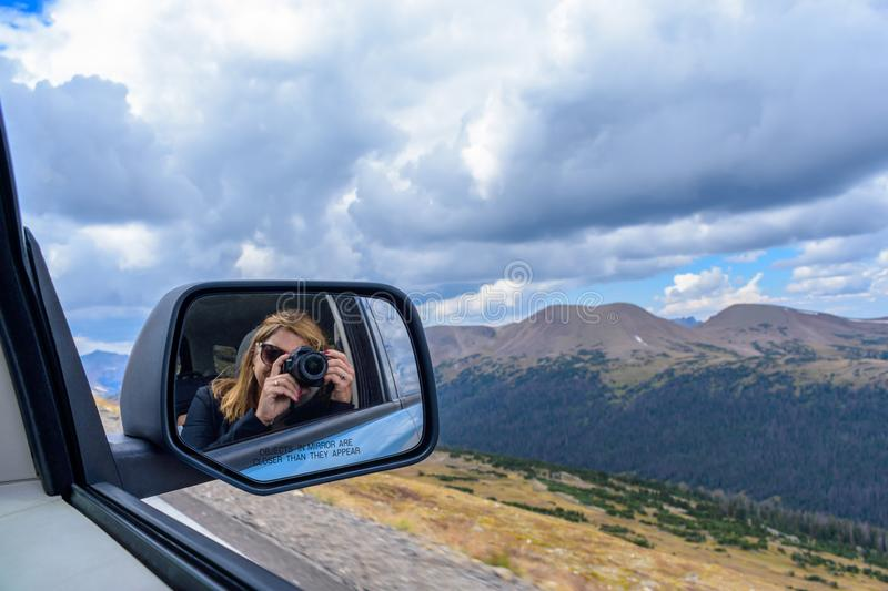 Woman taking photo of rocky mountains out car window reflected i. Woman refection in car side mirror holding digital camera taking a picture of the rocky royalty free stock image