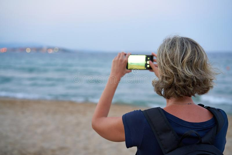 Woman taking a photo of a sea on smart phone on sunset royalty free stock photos