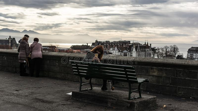 Woman Taking Photo While Sitting on the Bench Behind the Building Scenery stock photos